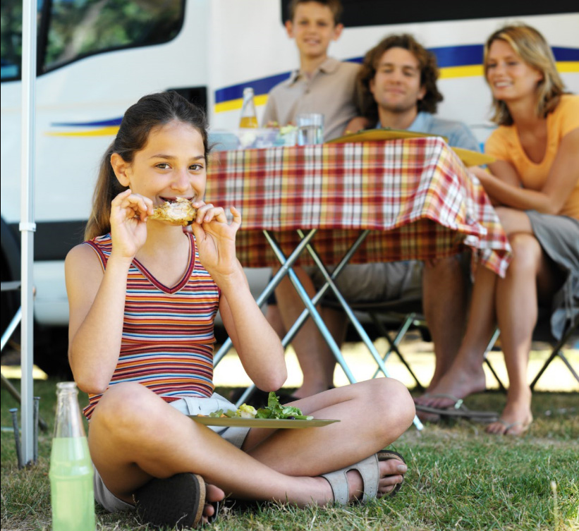 Young girl sits on lawn eating lunch in front of her family seated at a picnic table and their RV.