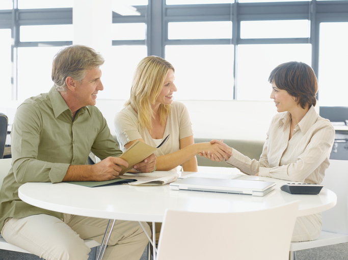 Couple seated at table shaking hands with a loan officer