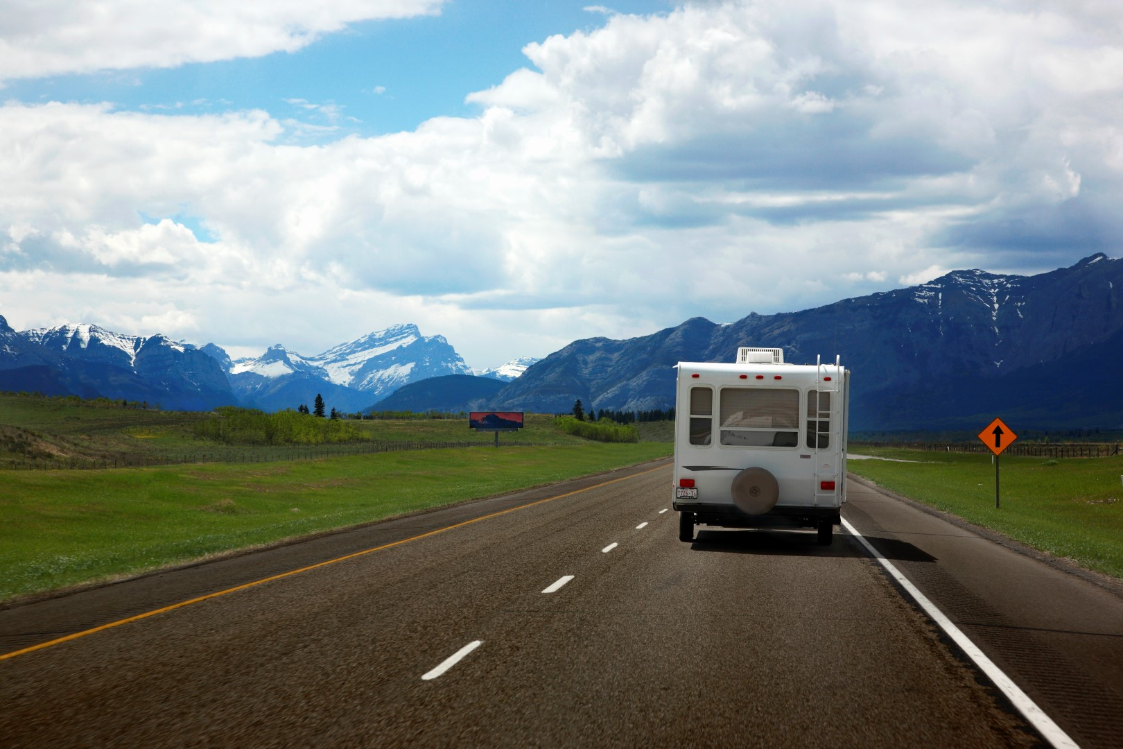 Rear view of a small RV being towed down a highway.