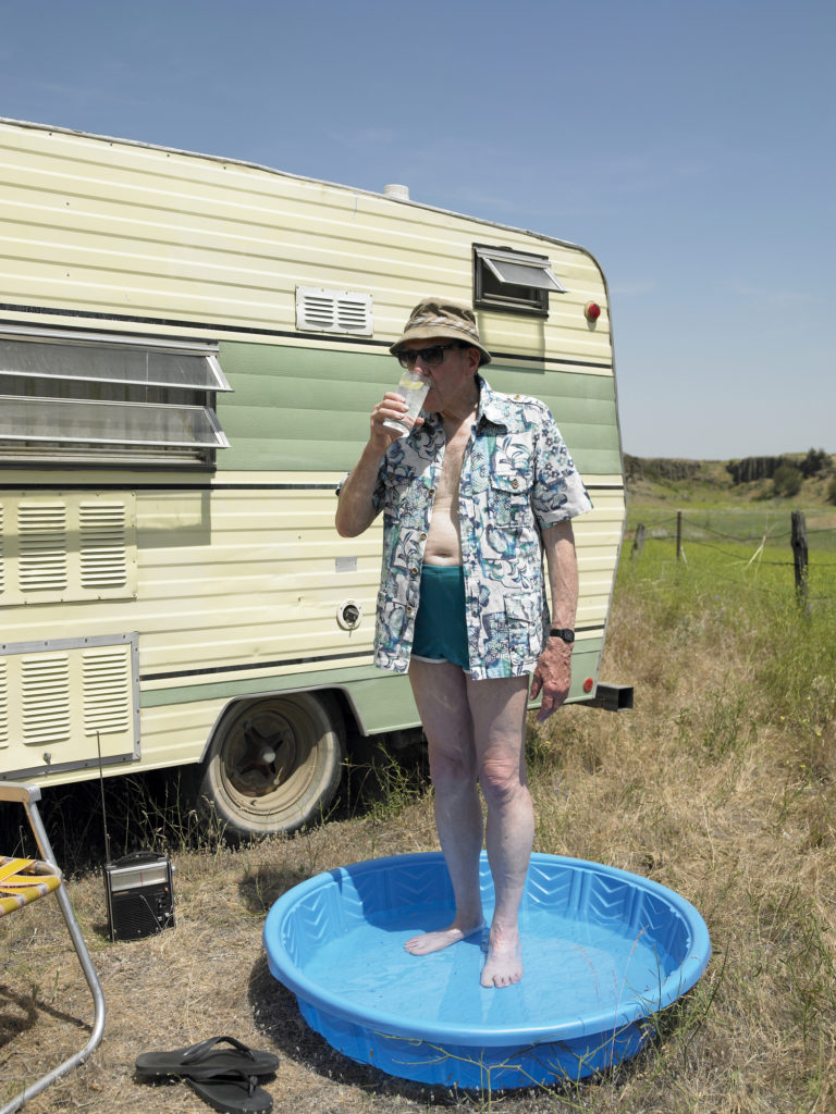 Older man standing in a wading pool next to an old RV