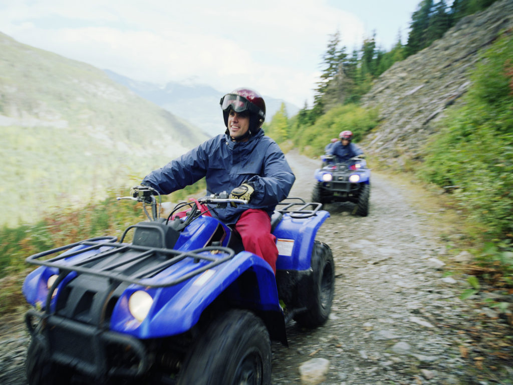 Man driving ATV with group on mountain road