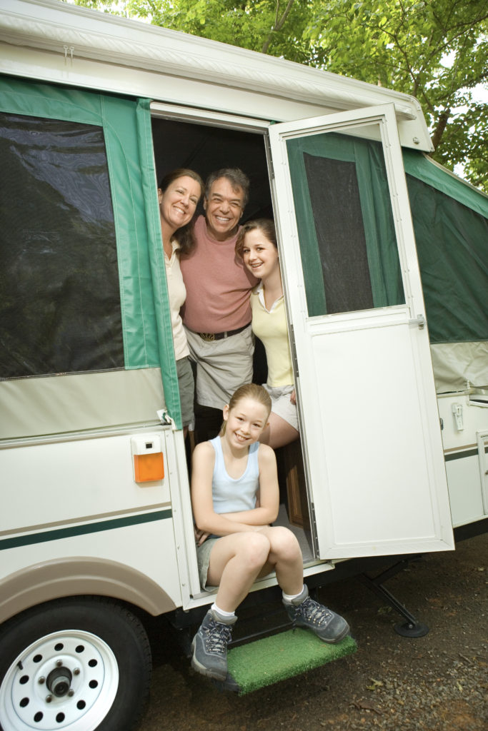 Smiling family in the doorway of a small RV.