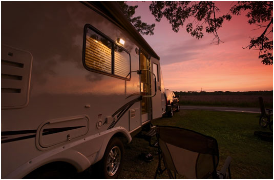 Side view of a luxury travel trailer in the sunset