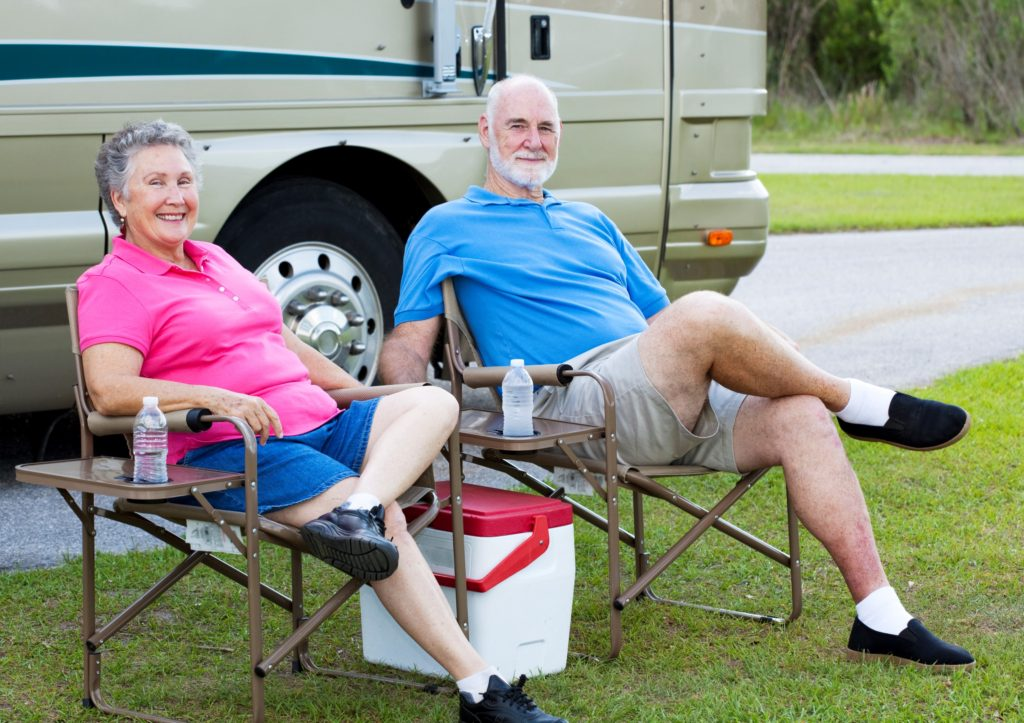 Senior couple sits outside their used motorhome