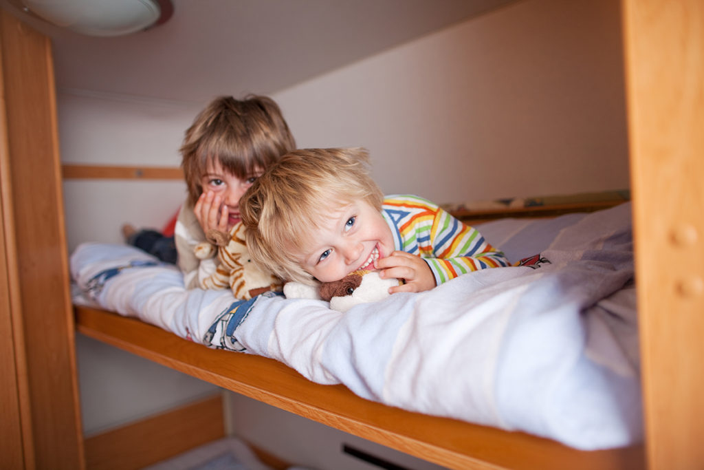 Two smiling young boys enjoying the top bunk in a bunkhouse trailer