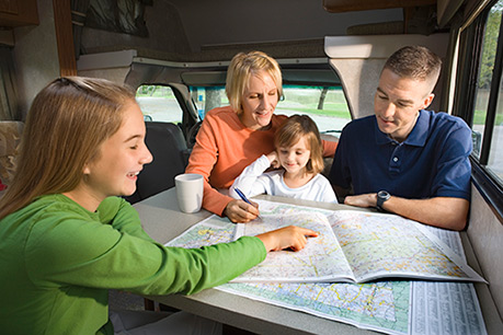 Family of four in RV smiling and looking at maps.