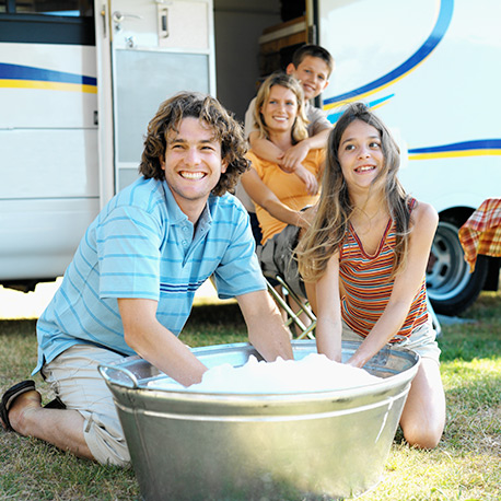 Happy family outside RV with bucket of soapy water.