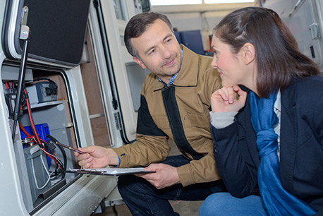 Man and woman checking electronics in RV with checklist