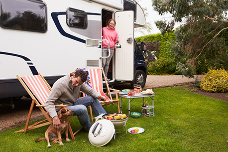 Man cooking food on a barbeque with a dog and woman outside motorized RV.