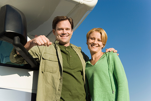 Smiling couple leaning on an RV.