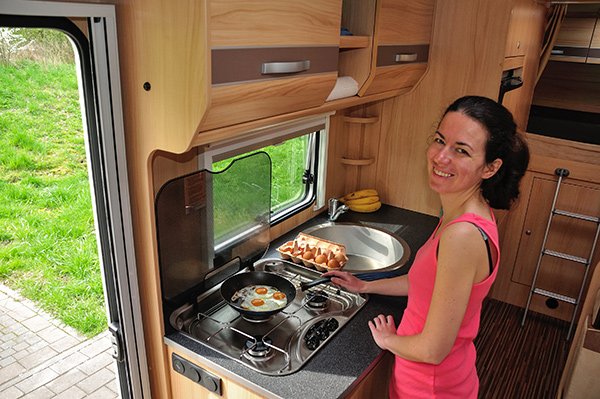 Woman cooking eggs in RV kitchen.