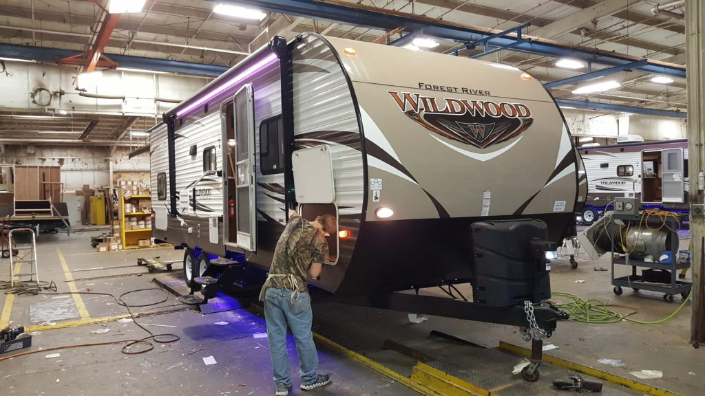 RV factory worker finishing a build of a Wildwood RV.