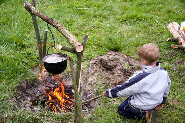 Young boy cooking in a pot hanging over a fire.