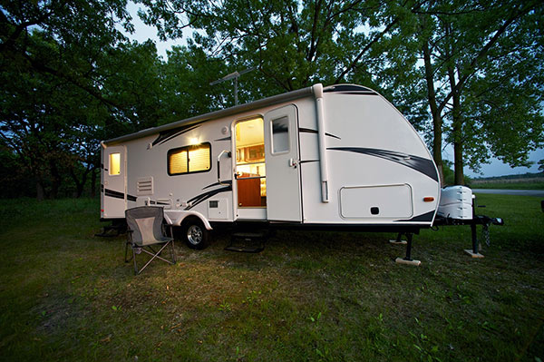 25 foot RV boondocking with doors open parked near trees.