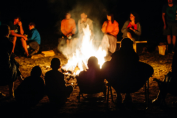 Several families sitting around a bright campfire at night.