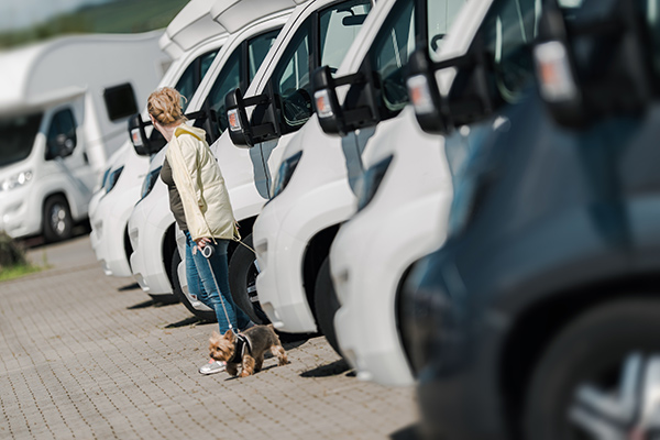 Woman with a dog browsing through an RV lot.