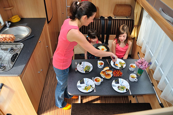 Mother setting table for family of four in RV dinette.