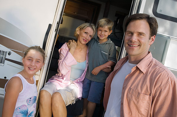 Full time RV family with parents and two children in the doorway of an RV.