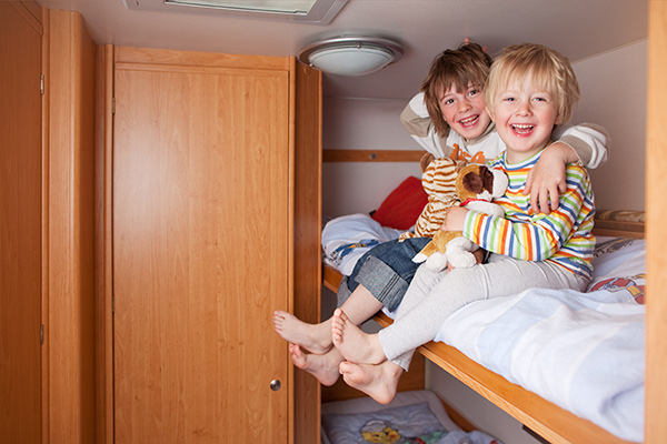 Two boys sitting in a bunk in an RV.