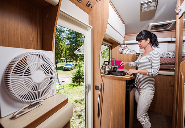Woman living in small RV parked at a campground.