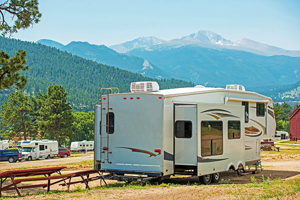 Expandable fifth wheel RV parked at a campsite in Colorado.