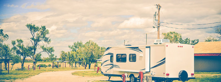 An RV at a campsite hooked up to the RV park's power.