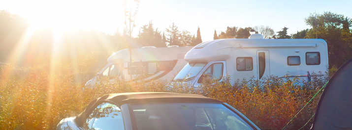 Two RVs with a bright sun shining down on them in a campground.
