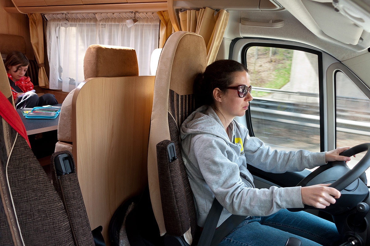 A mother driving her motorhome with a child playing in the back.