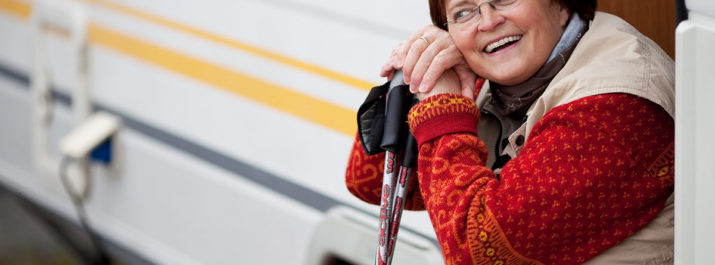 A woman with hiking poles sitting on the stairs of her RV.