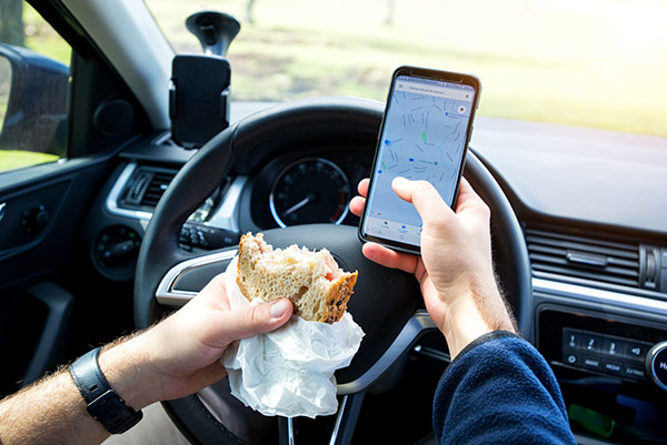A person driving with a phone and sandwich in their hands.