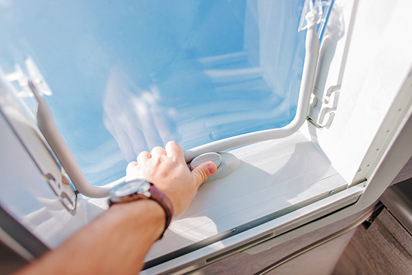 A person opening an RV vent lid