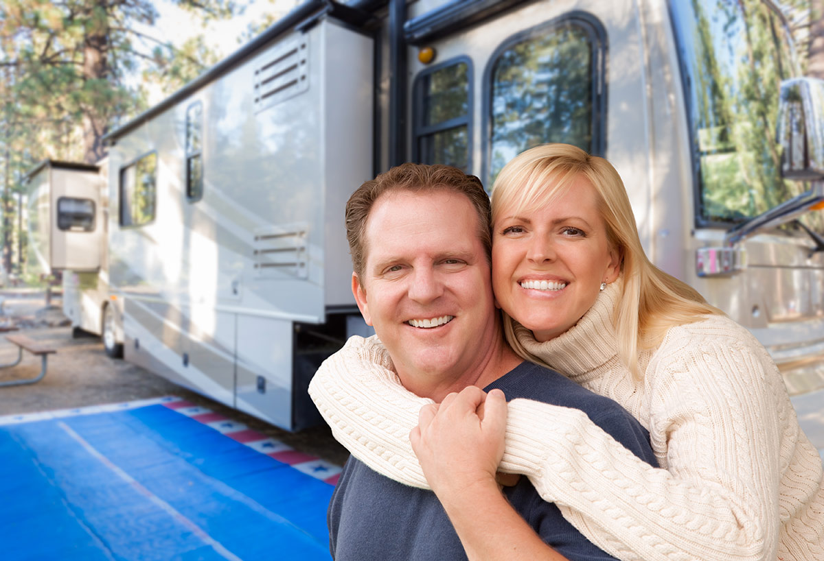 New RV owners standing in front of their RV