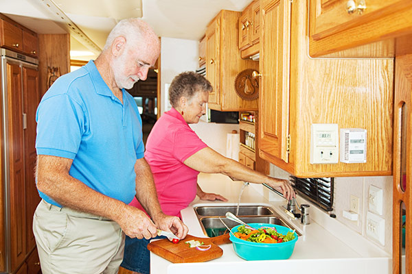 Senior couple making a salad together in their RV kitchen