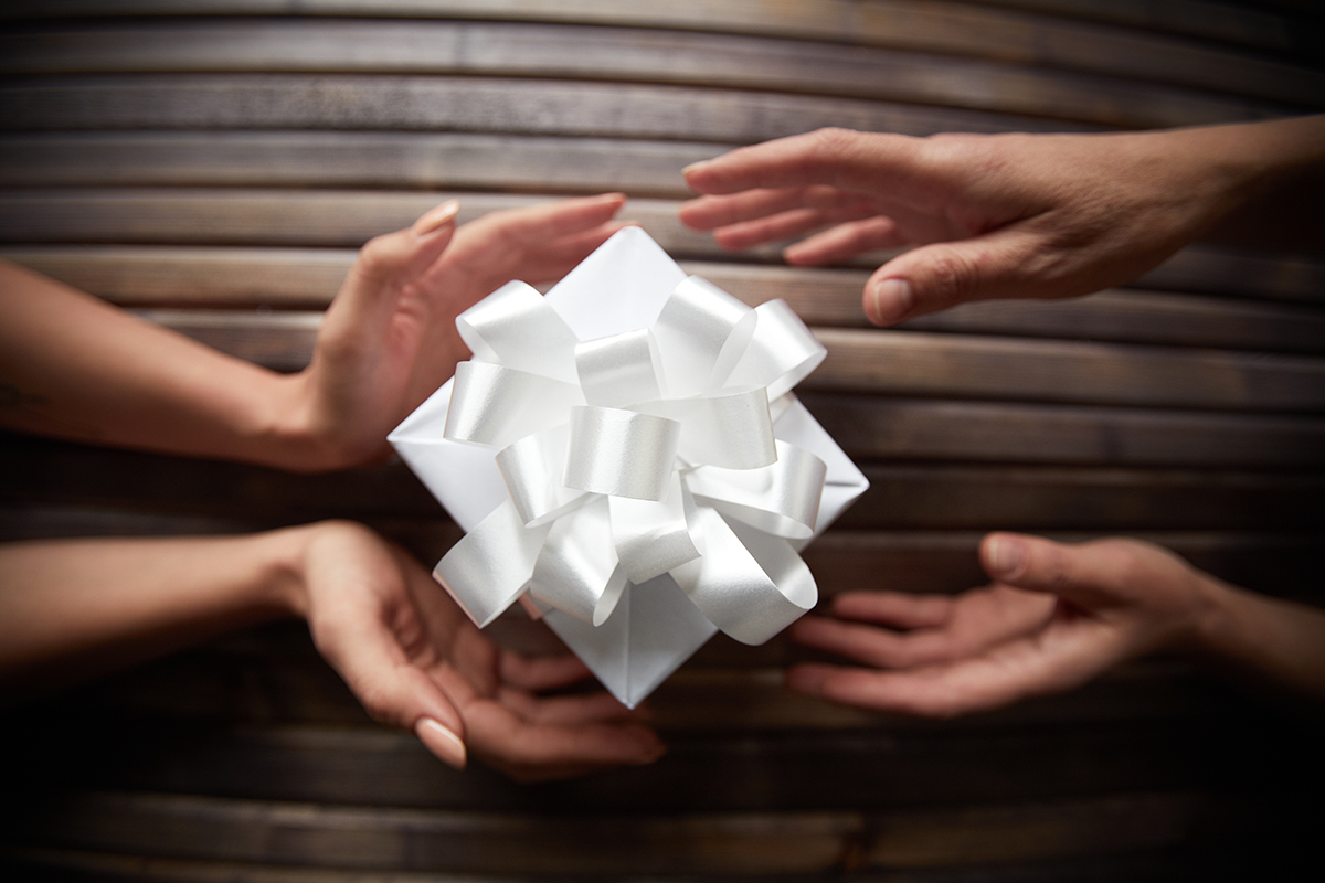 Hands pushing a gift-wrapped box towards another person