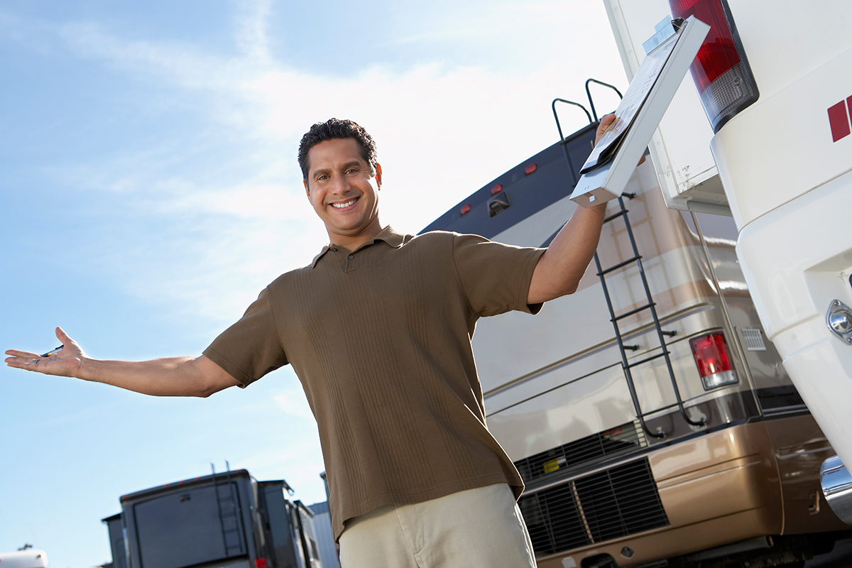 A smiling man with a clipboard stands with open arms near a row of RVs