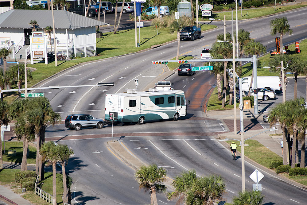 A motorhome with an RV toad makes a left turn onto a palm-tree lined road