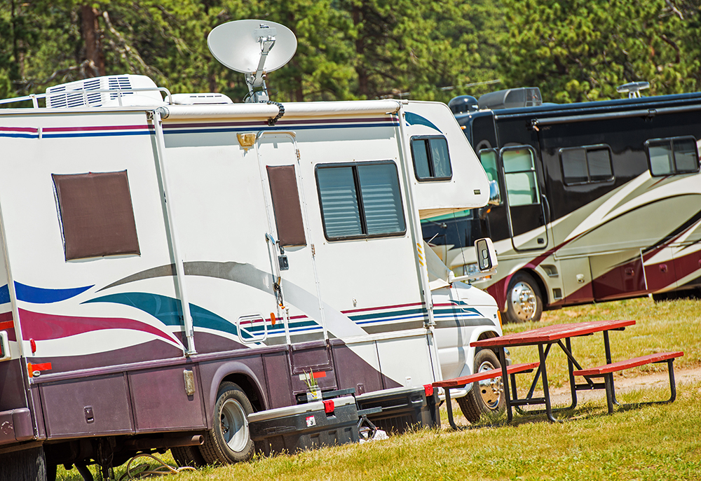 Two RVs parked at a campground