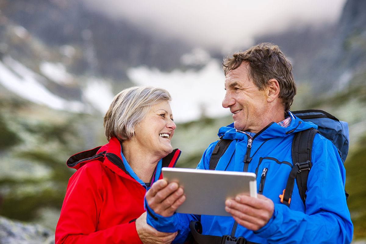 A senior couple looking at the best RV websites on a tablet during a camping trip.