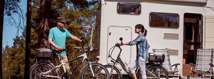 A couple standing with bikes and chairs in front of an RV.