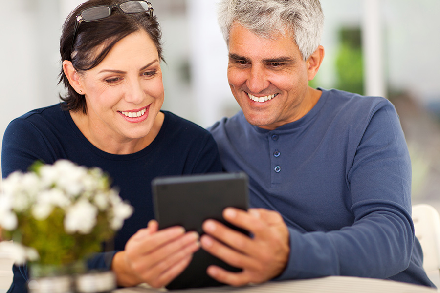 A man and woman are smiling as they hold a tablet and watch an RV YouTube channel together.