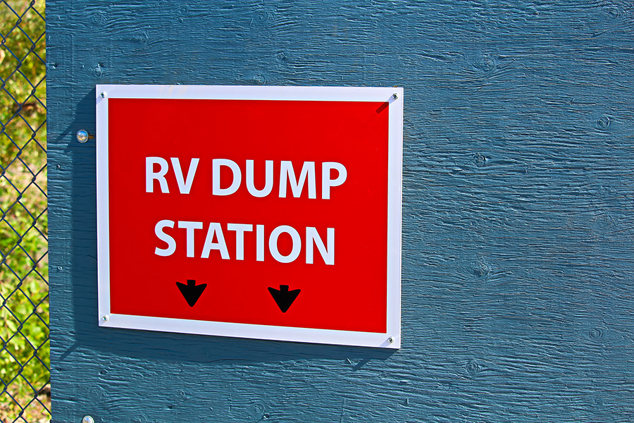 A bright red and white sign indicates where an RV Dump Station is located.