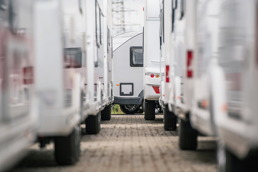 Looking between long rows of parked trailers ready for RV pre-purchase inspection