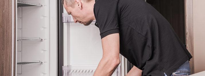 A man repairing a fridge in an RV.