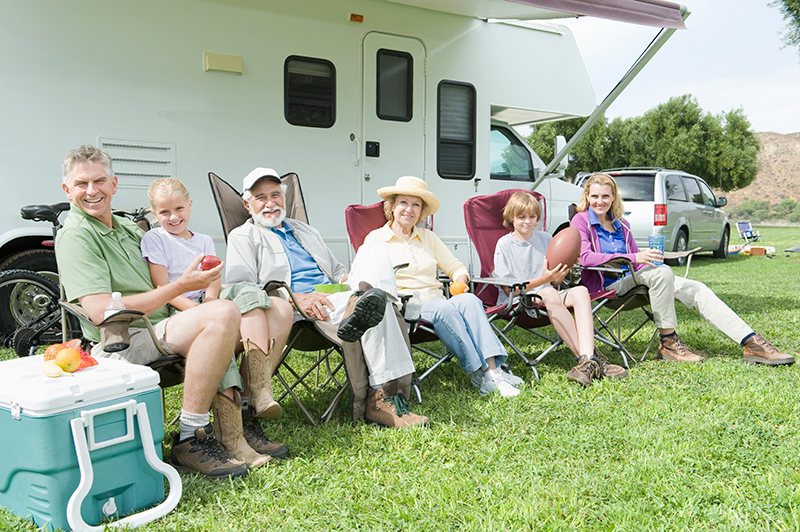 A family sitting in front of their RV playing an RV camping game.