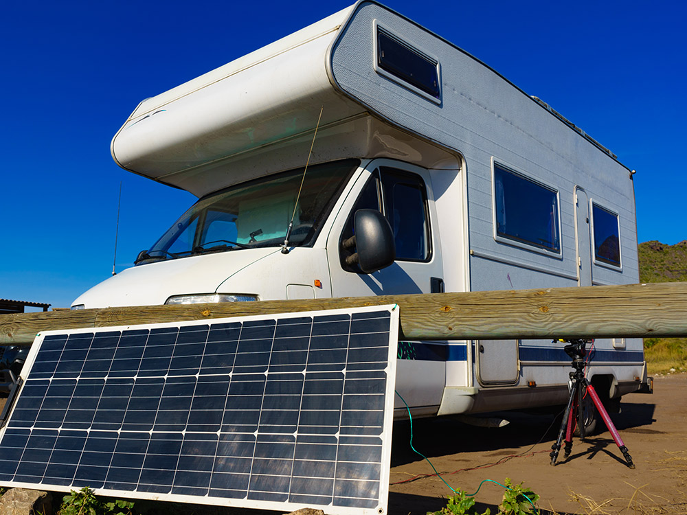 A camper harnesses the sun's energy with one of the many portable RV solar power options available including DIY versions.