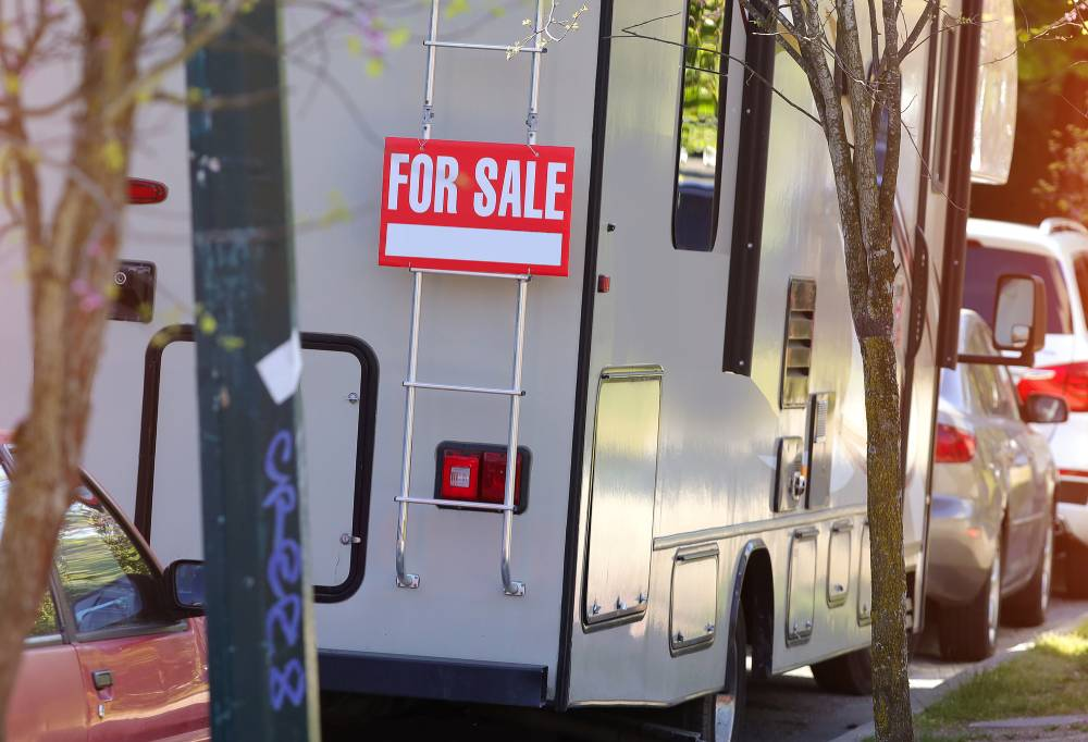 A person selling an RV with a sign on the back