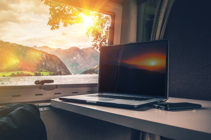 An RV office with a view. No screensaver can rival the incredible mountain lakeside view from the window of this RV office.