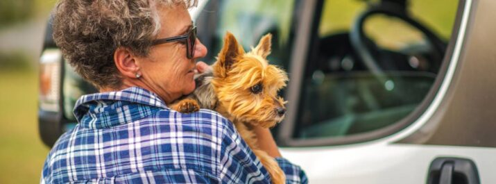 A woman stands near an RV holding her small dog. RVing with dogs is important since they can be like a member of the family.